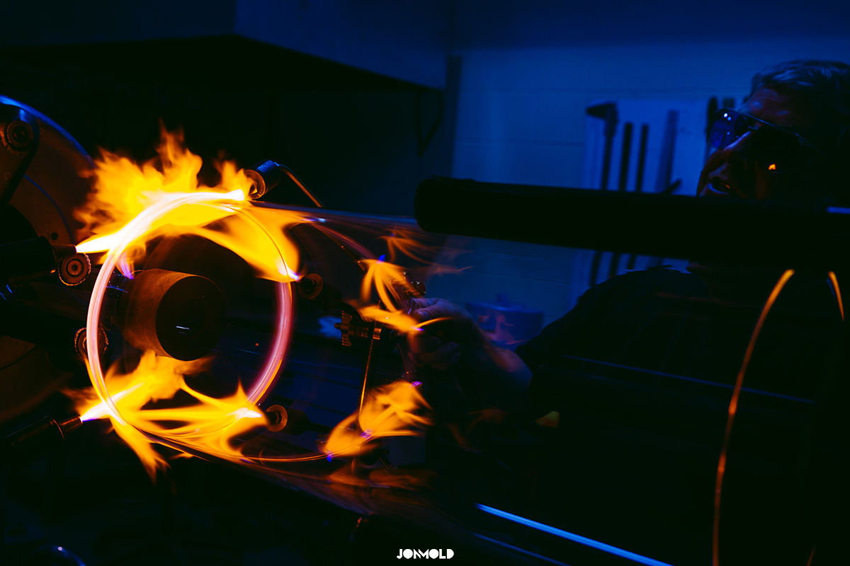 rolling large glass tubes with flames