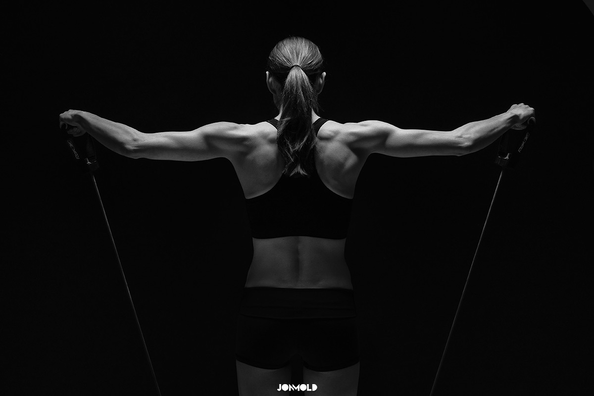 Female fitness model muscular back with weights