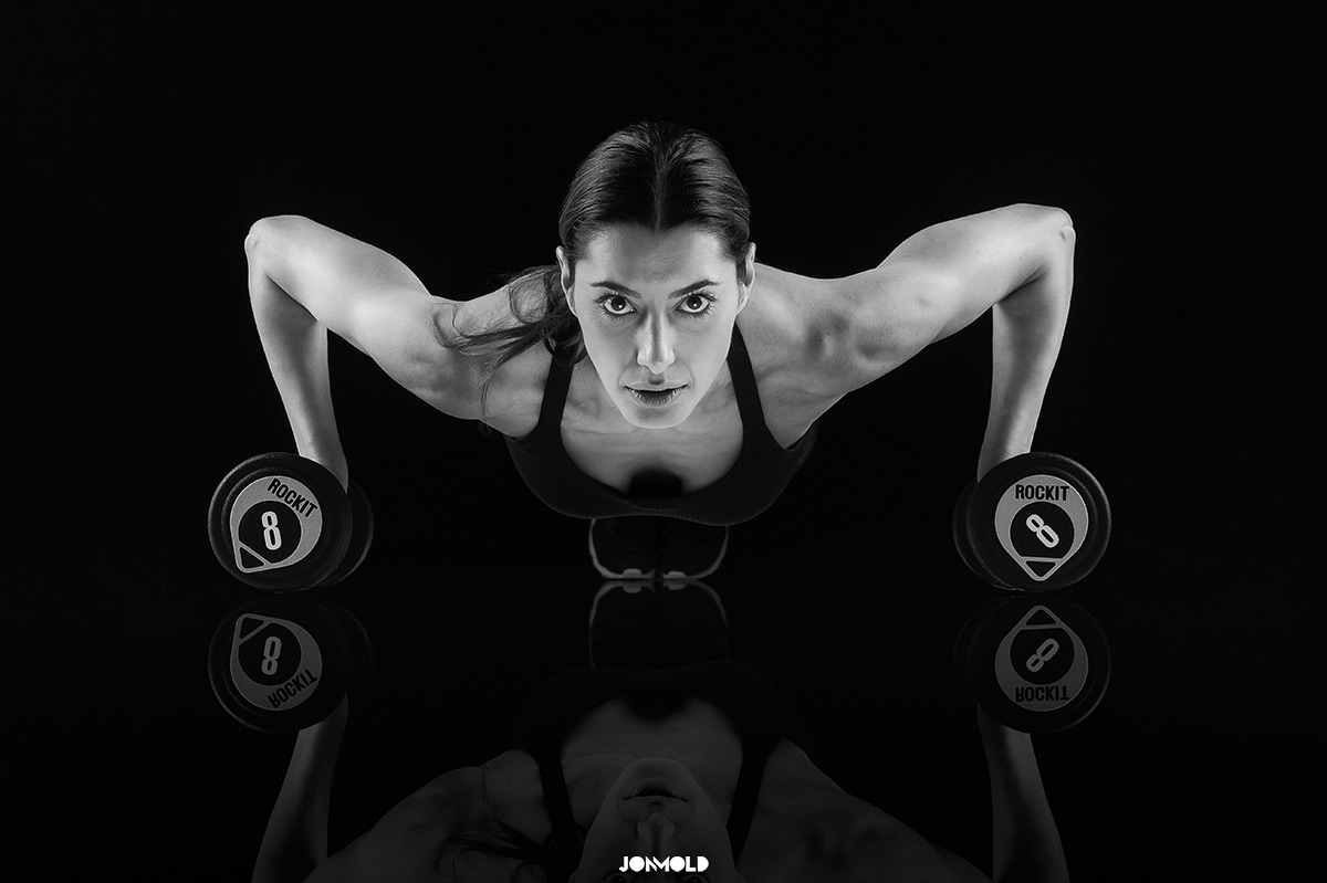 female fitness pushup with dumbells